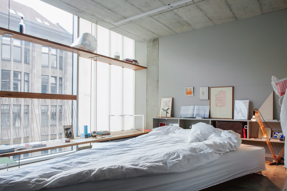 Inspiration for a medium sized industrial master bedroom in Berlin with grey walls, concrete flooring and no fireplace.
