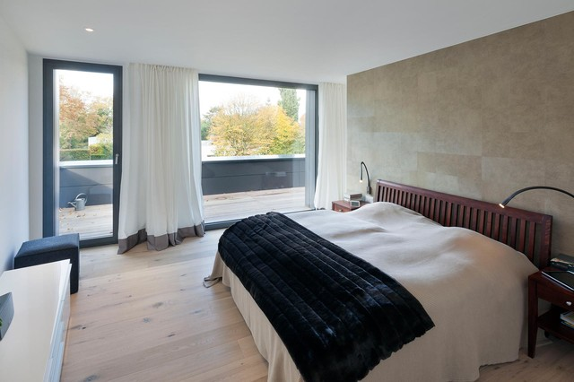 Example of a mid-sized trendy master light wood floor bedroom design in Cologne with beige walls and no fireplace