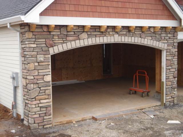 Cultured stone dundee traditional garage and shed for Wood veneer garage doors
