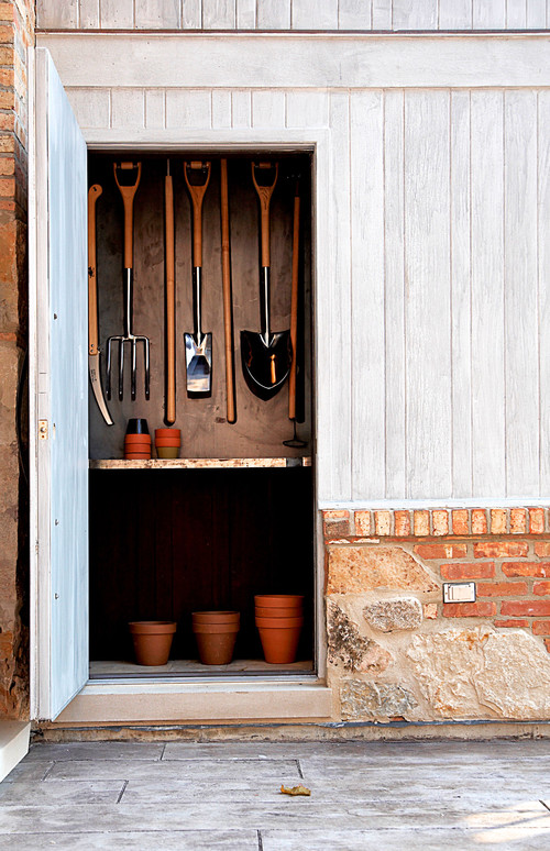 Tool shed with rakes, snow shovel, and other tools