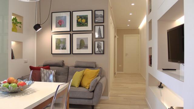 Esempio di un piccolo soggiorno scandinavo aperto con libreria, pareti beige, pavimento in gres porcellanato e TV a parete