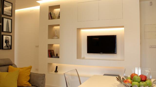 Immagine di un piccolo soggiorno design aperto con libreria, pareti beige, pavimento in gres porcellanato e TV a parete
