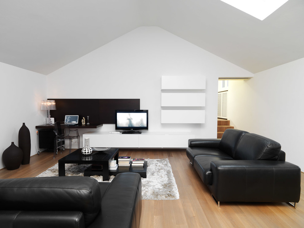 Mid-sized trendy light wood floor family room photo in Turin with white walls and a tv stand