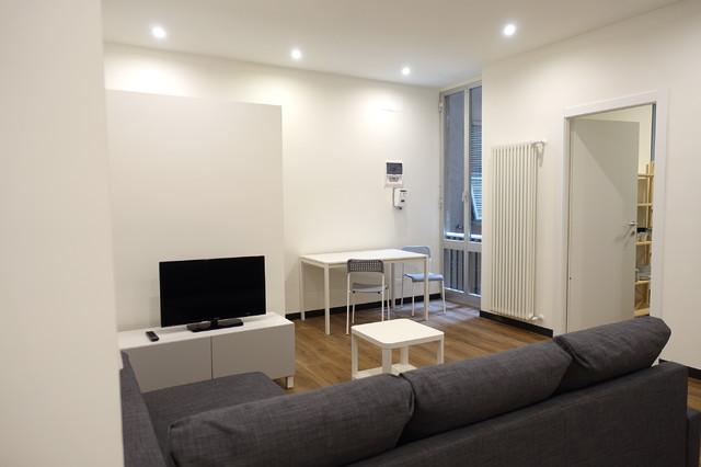 Esempio di un soggiorno contemporaneo di medie dimensioni e aperto con pareti bianche e pavimento in laminato