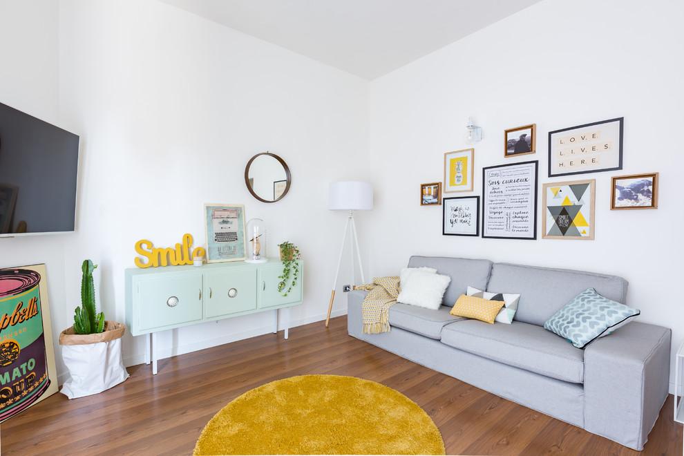 Immagine di un soggiorno nordico di medie dimensioni e aperto con pareti bianche, pavimento in legno massello medio, TV a parete e pavimento marrone