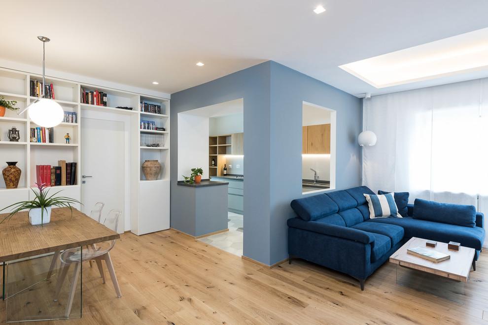 Ispirazione per un soggiorno minimal aperto con libreria, pareti blu, pavimento in legno massello medio e pavimento beige