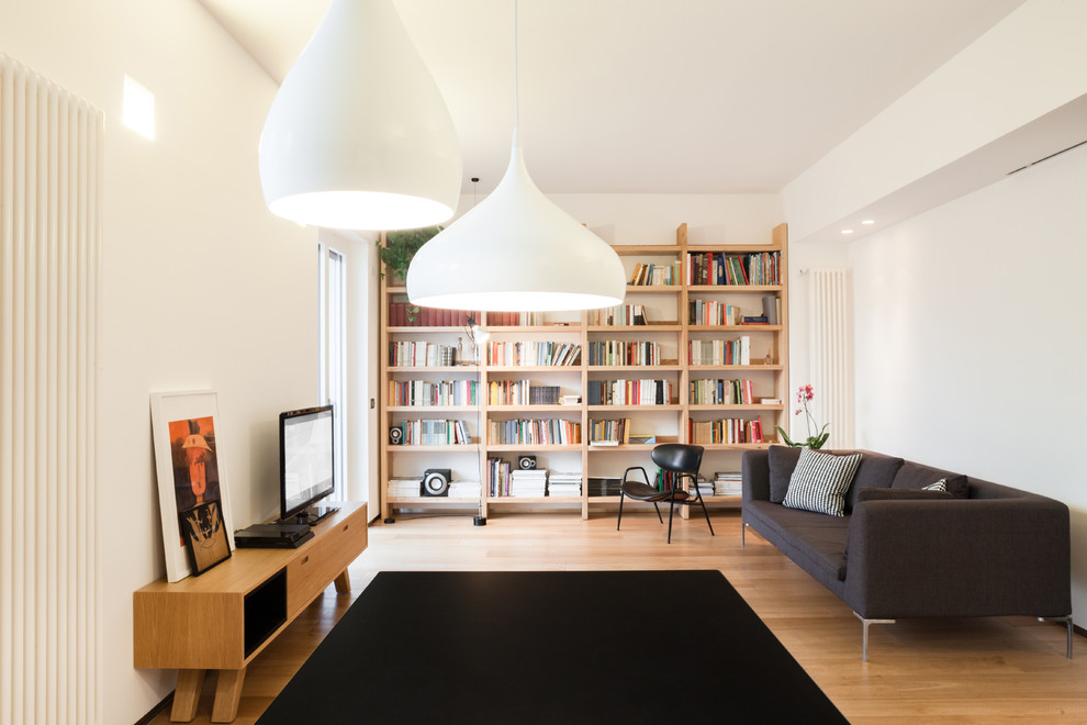 Example of a danish enclosed light wood floor and beige floor living room library design in Cagliari with white walls and a tv stand
