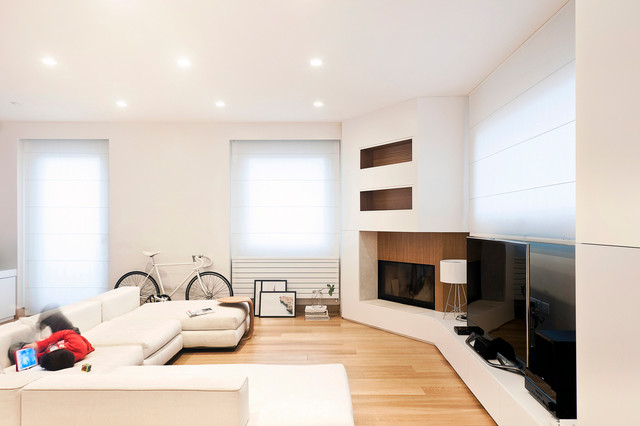 Example of a danish light wood floor family room design in Cagliari with white walls, a tv stand, a wood fireplace surround and a corner fireplace