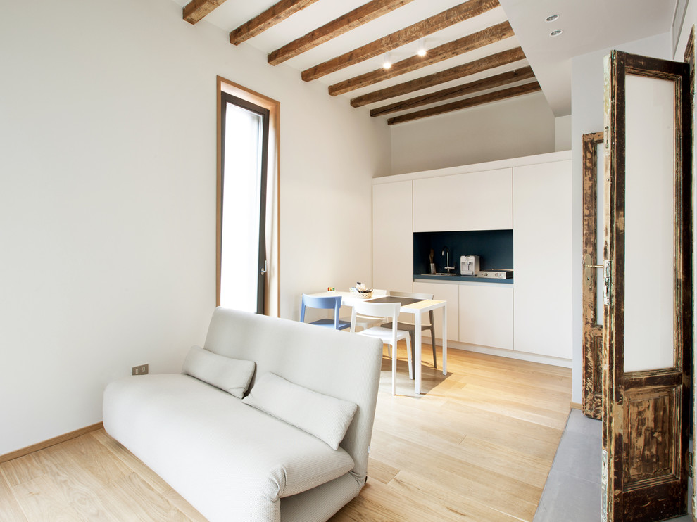 Living room - mid-sized contemporary open concept light wood floor living room idea in Milan with white walls