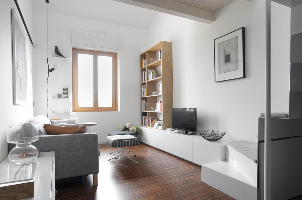 Danish open concept dark wood floor living room photo in Milan with white walls and a tv stand