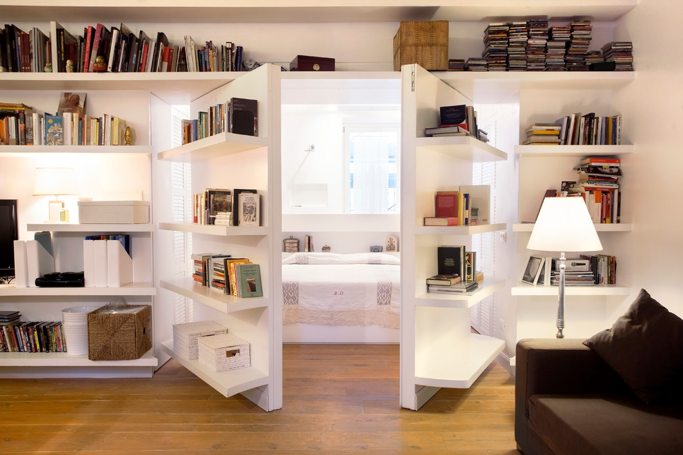 Example of a trendy enclosed light wood floor family room library design in Rome with white walls
