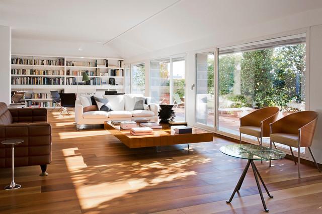 Esempio di un grande soggiorno minimal aperto con pareti bianche e pavimento in legno massello medio
