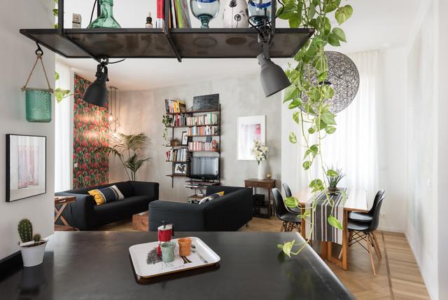 Esempio di un soggiorno design aperto con libreria, pareti grigie, parquet chiaro, TV autoportante e pavimento marrone