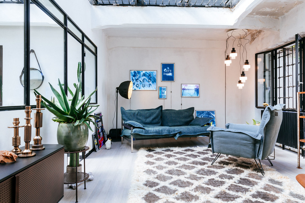 Inspiration for a mid-sized industrial enclosed gray floor living room remodel in Milan with white walls and no tv