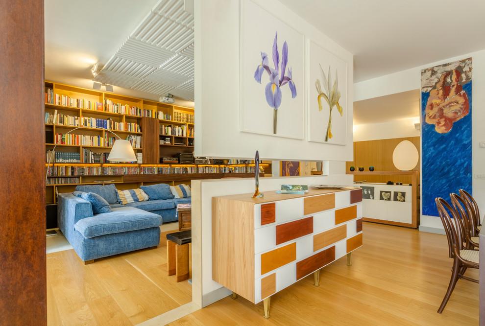 Idee per un soggiorno contemporaneo aperto con libreria, pareti bianche, pavimento in legno massello medio e pavimento marrone