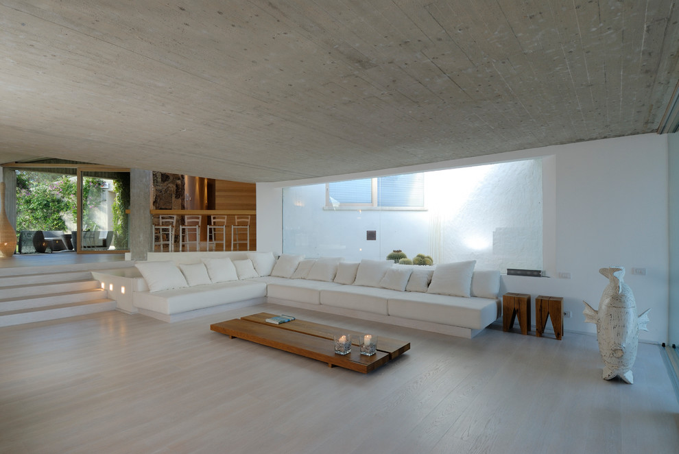 Living room - large contemporary open concept light wood floor and beige floor living room idea in Other with white walls
