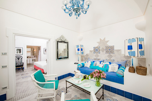Family room - large mediterranean open concept family room idea in Naples with white walls and no fireplace