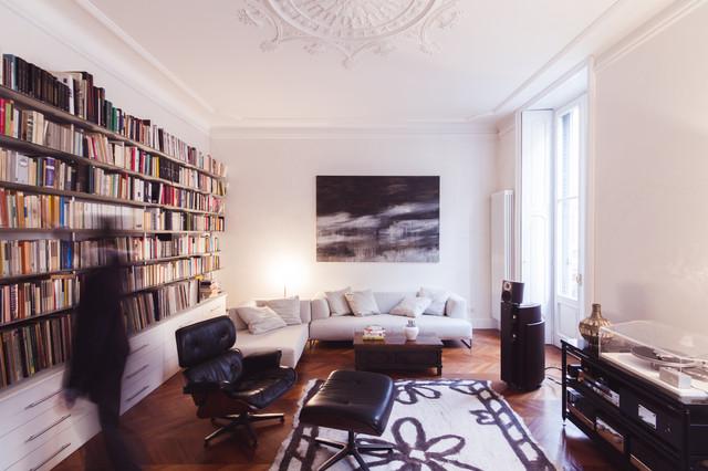 Cette image montre un salon avec une bibliothèque ou un coin lecture design avec un mur blanc et un sol en bois clair.
