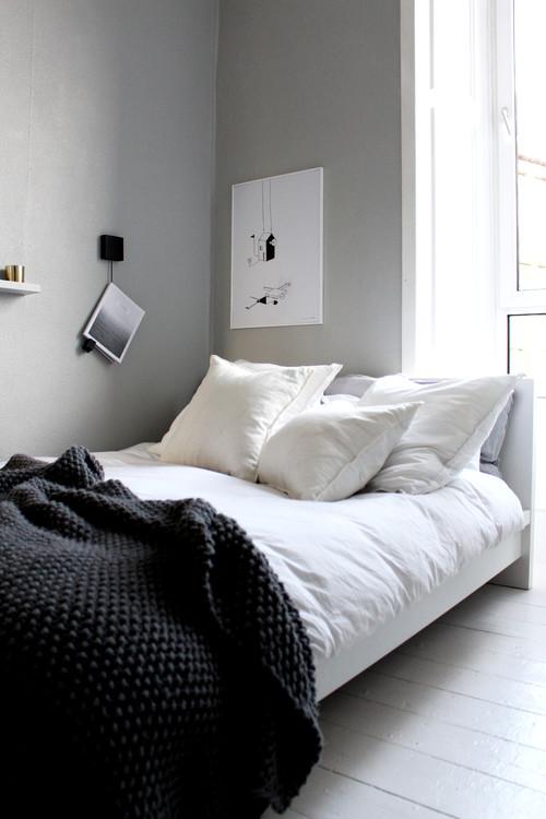 Soveværelse med lyse grå vægge og hvide gulve. Meget rent og lækkert med grafisk sort/hvid kunst på væggen, hvidt sengetøj og et mørkt sengetæppe