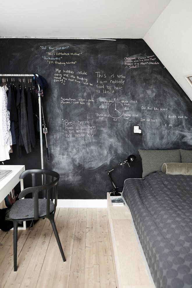 Example of a small danish light wood floor bedroom design in Wiltshire with black walls