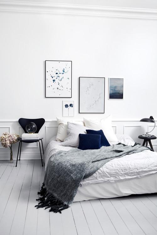 Soveværeles med smukke hvide højepaneler og hvide gulve. Kunst på væggen fra Trine Holbæk