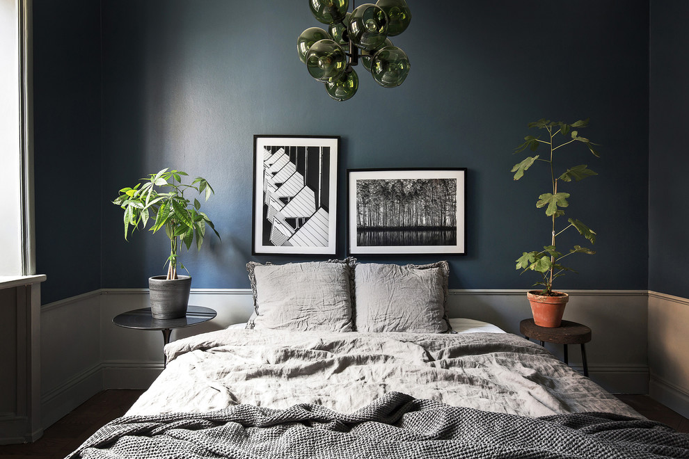 Example of a small danish master dark wood floor bedroom design in Stockholm with blue walls
