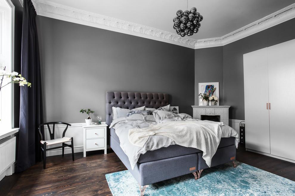Bedroom - scandinavian master dark wood floor and brown floor bedroom idea in Stockholm with gray walls, a corner fireplace and a tile fireplace