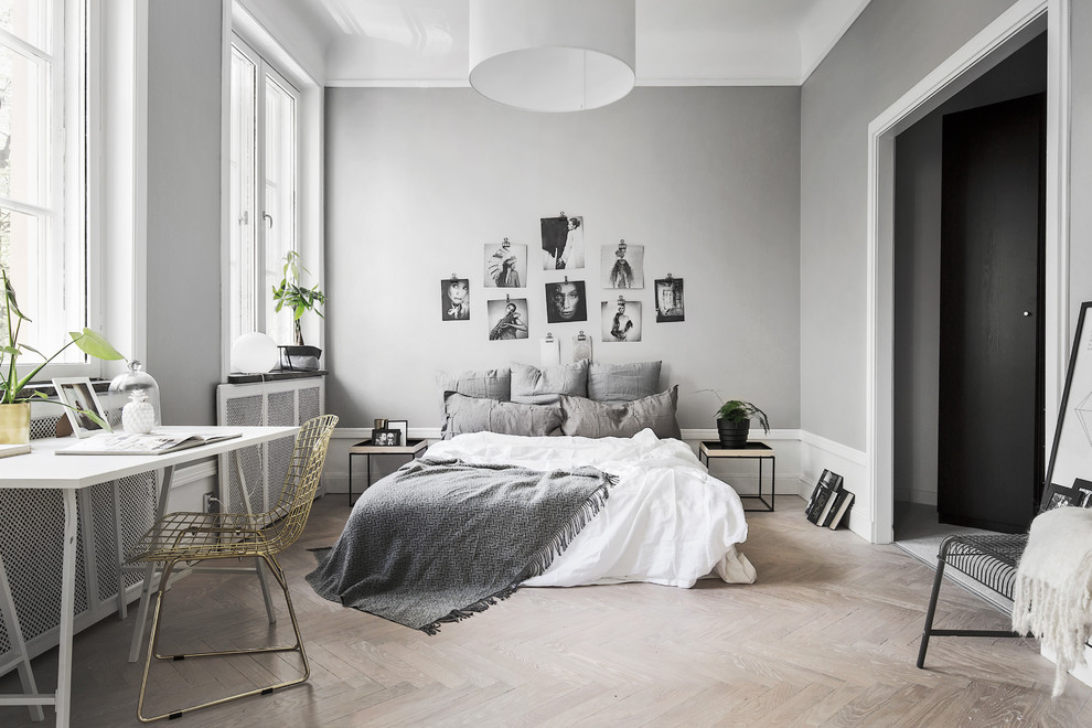 Mid-sized danish master light wood floor bedroom photo in Stockholm with gray walls