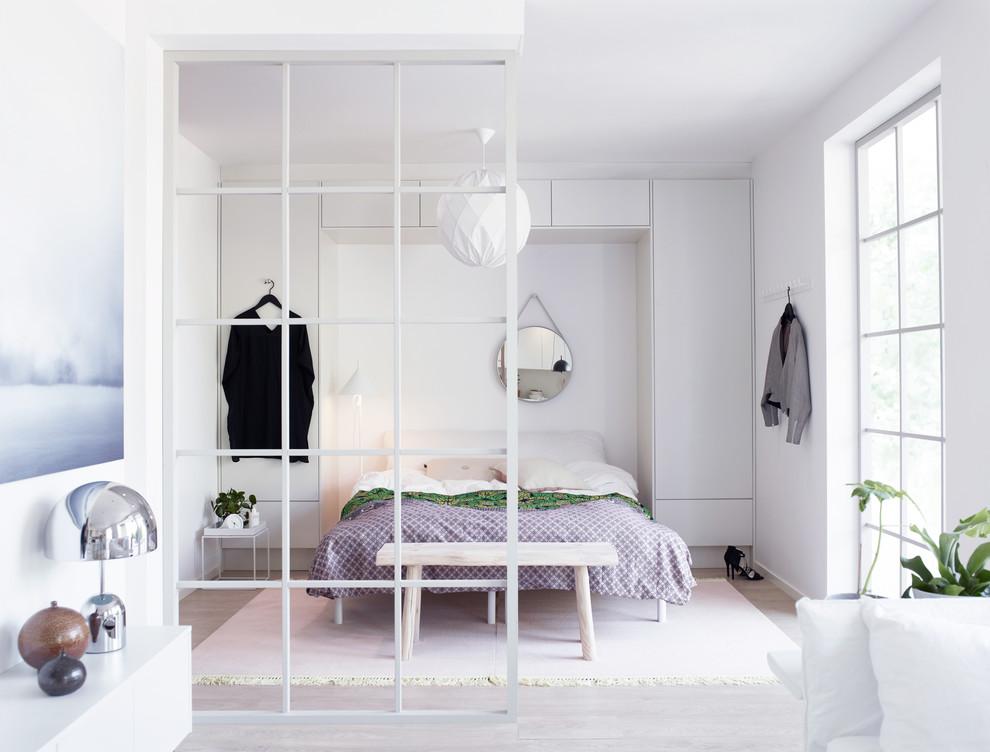 Bild på ett stort minimalistiskt huvudsovrum, med flerfärgade väggar och ljust trägolv