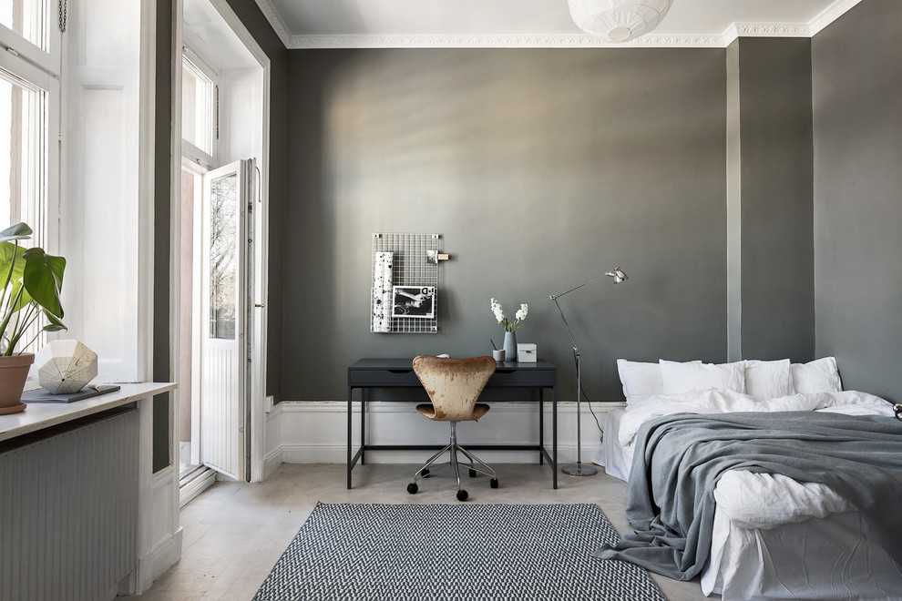 Example of an urban master light wood floor and gray floor bedroom design in Stockholm with gray walls
