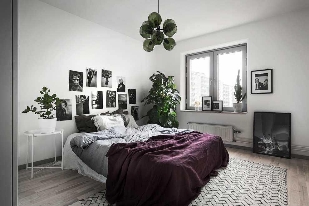 Example of a mid-sized danish master light wood floor bedroom design in Stockholm with gray walls and no fireplace