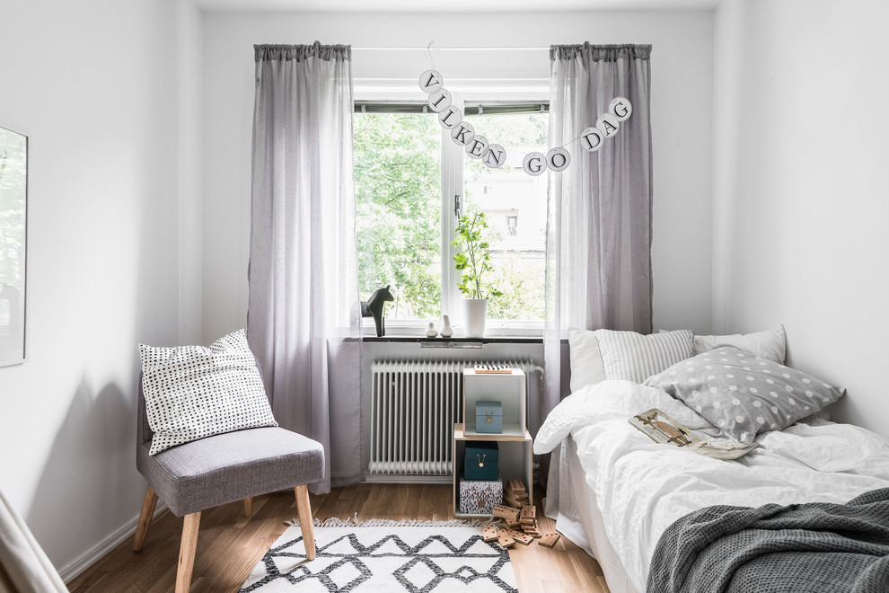 Mid-sized danish guest medium tone wood floor bedroom photo in Gothenburg with white walls