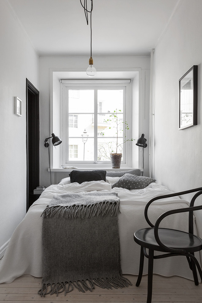 Bedroom - small scandinavian master light wood floor bedroom idea in Gothenburg with white walls and no fireplace