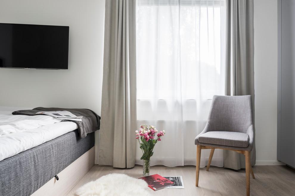 Nordisk inredning av ett mellanstort sovrum, med beige väggar och ljust trägolv