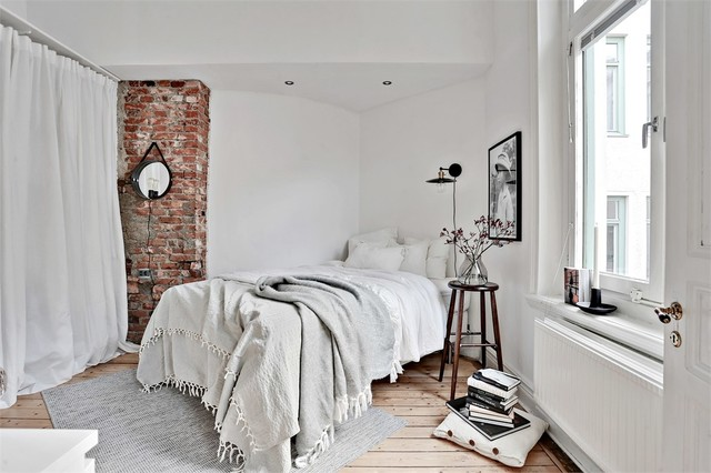 Mid-sized danish master light wood floor bedroom photo in Gothenburg with white walls