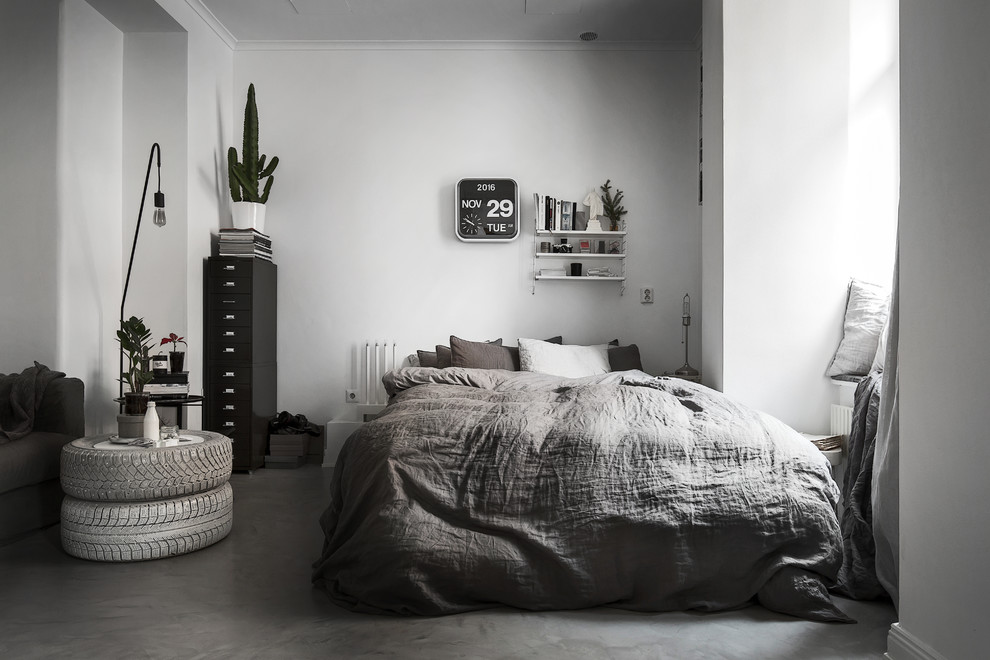 Example of a danish concrete floor bedroom design in Stockholm with white walls
