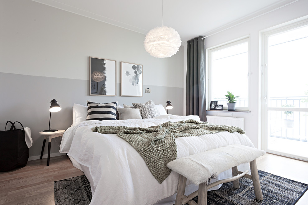 This is an example of a medium sized scandi guest bedroom in Gothenburg with light hardwood flooring, white walls and brown floors.