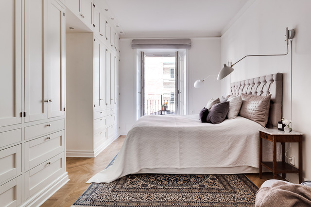 Example of a mid-sized danish master medium tone wood floor bedroom design in Stockholm with white walls and no fireplace