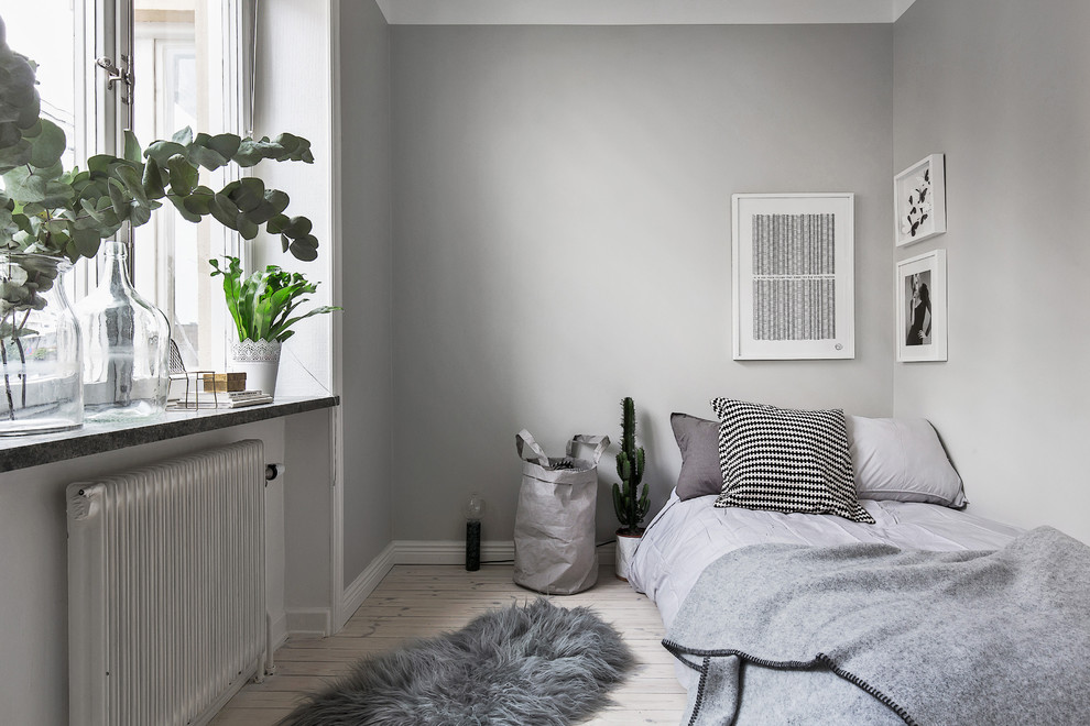 Small danish guest light wood floor bedroom photo in Stockholm with gray walls and no fireplace