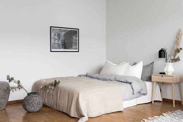 Modelo de dormitorio principal, nórdico, pequeño, sin chimenea, con paredes blancas y suelo de madera en tonos medios