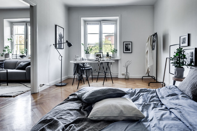 Inspiration for a large scandinavian master light wood floor bedroom remodel in Stockholm with white walls and no fireplace