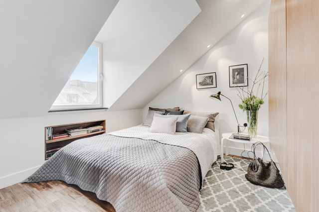 This is an example of a medium sized scandinavian master bedroom in Stockholm with white walls, light hardwood flooring, no fireplace and brown floors.