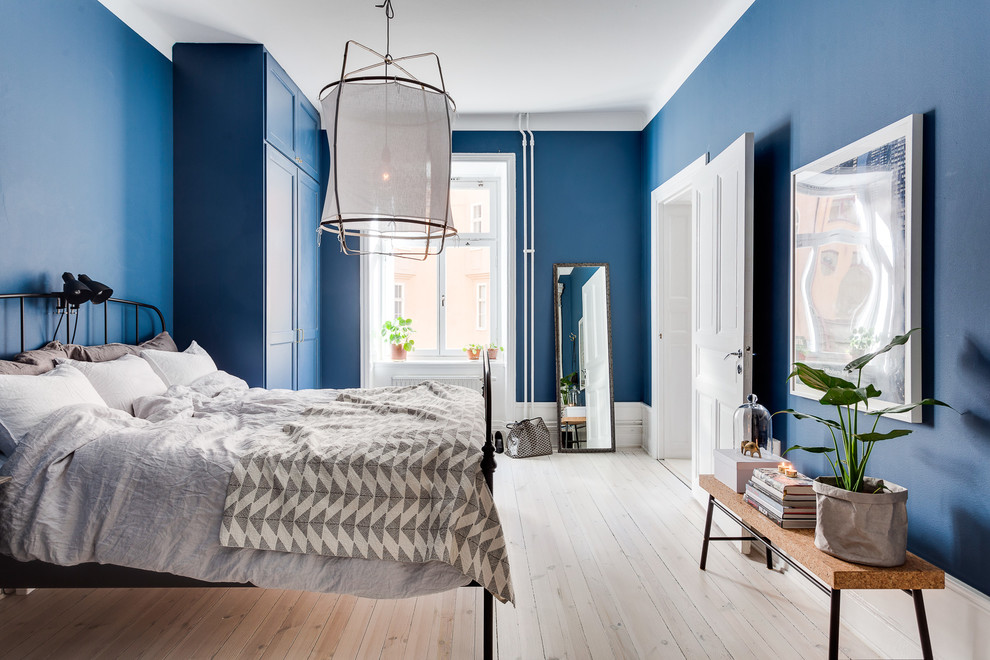 Example of a large transitional master light wood floor bedroom design in Stockholm with blue walls and no fireplace
