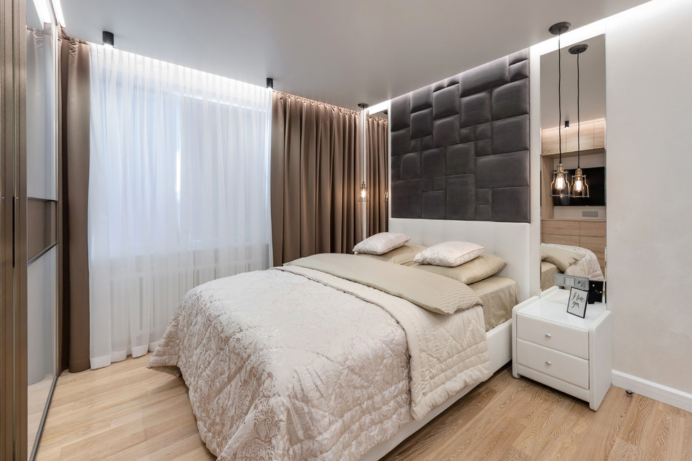 Mid-sized trendy master laminate floor and brown floor bedroom photo in Saint Petersburg with white walls