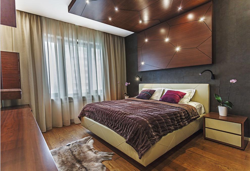 Создайте стильный интерьер: спальня среднего размера в современном стиле с серыми стенами и паркетным полом среднего тона для хозяев - последний тренд
