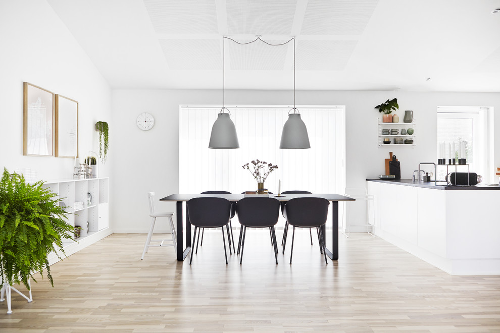 Inspiration for a mid-sized scandinavian kitchen/dining combo in Wiltshire with white walls, light hardwood floors and no fireplace.