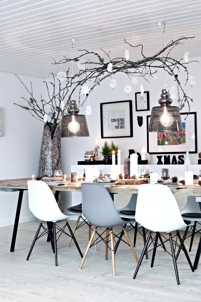 Inspiration for a mid-sized scandinavian light wood floor and white floor enclosed dining room remodel in Other with white walls