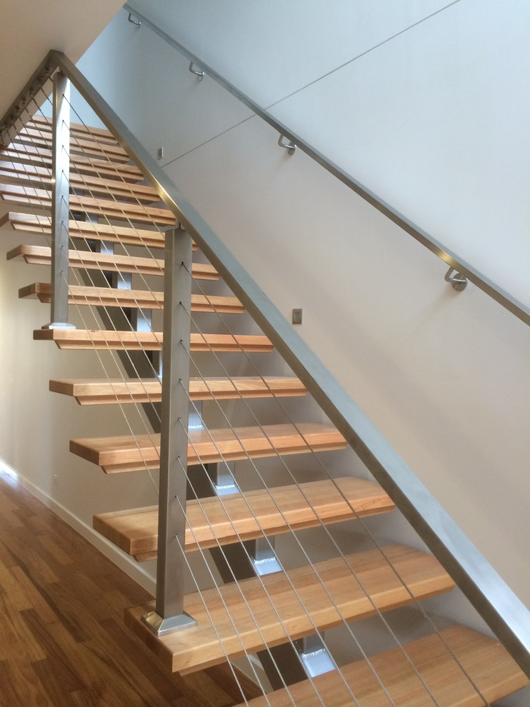 Example of a minimalist wooden straight metal railing staircase design in Melbourne