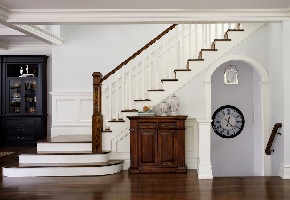 Example of a mid-sized classic wooden l-shaped staircase design in New York with painted risers