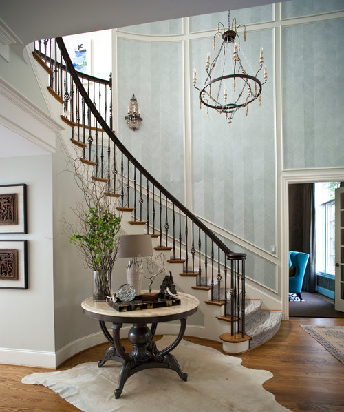 Foyer with round table and wood floor and curved staircase with panels filled with blue striped wallpaper